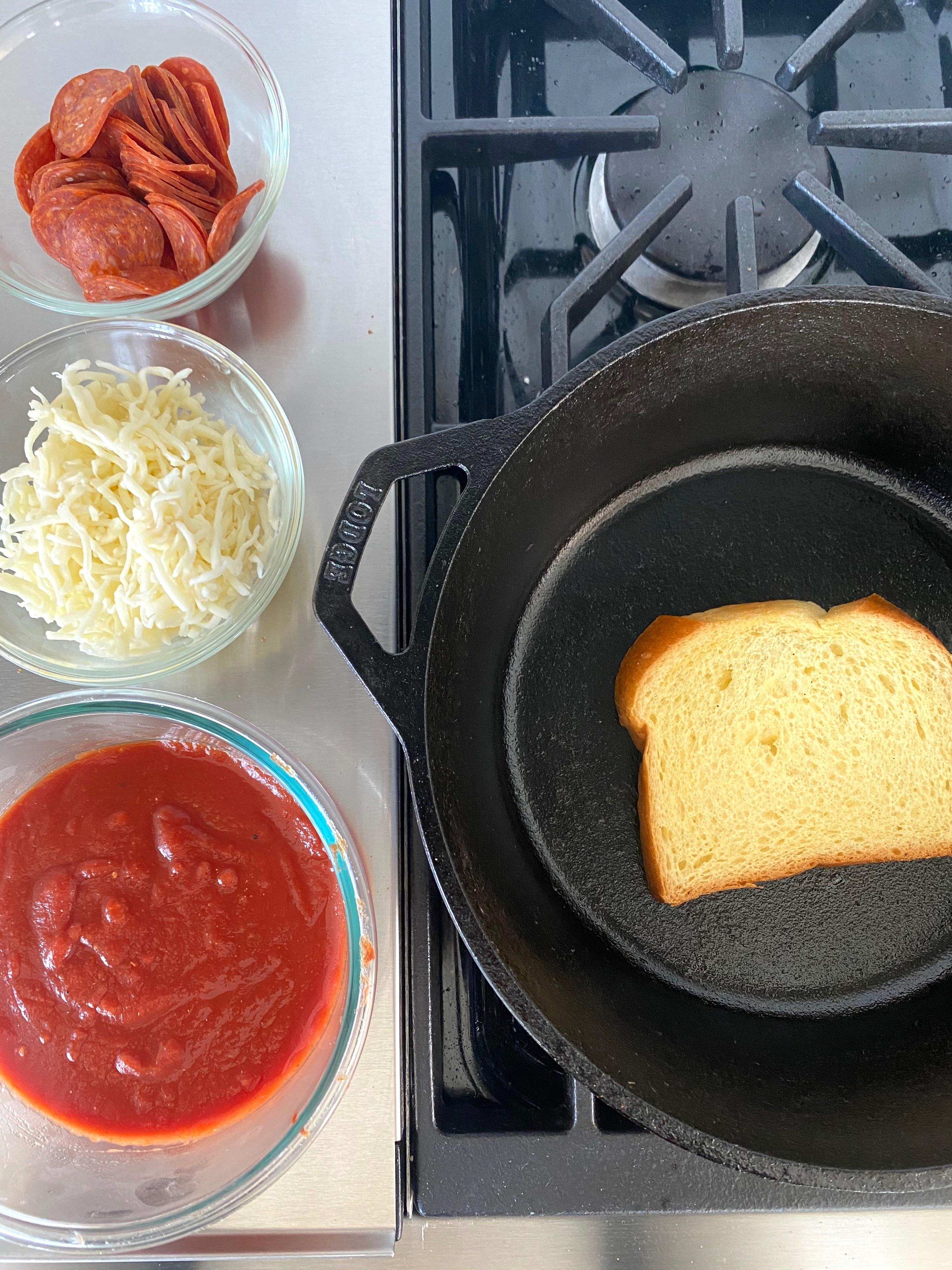 Tomato sauce, cheese, and pepperoni in small bowls next to a cast iron skillet with bread toasting inside.