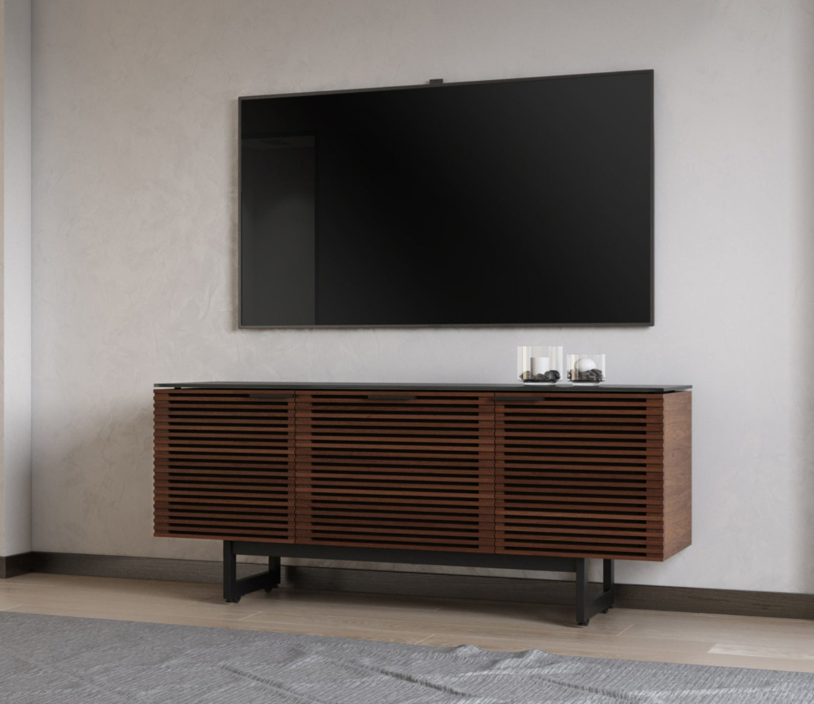 The triple-wide cabinet with wood slotted front and black metal legs under a TV in a living room.