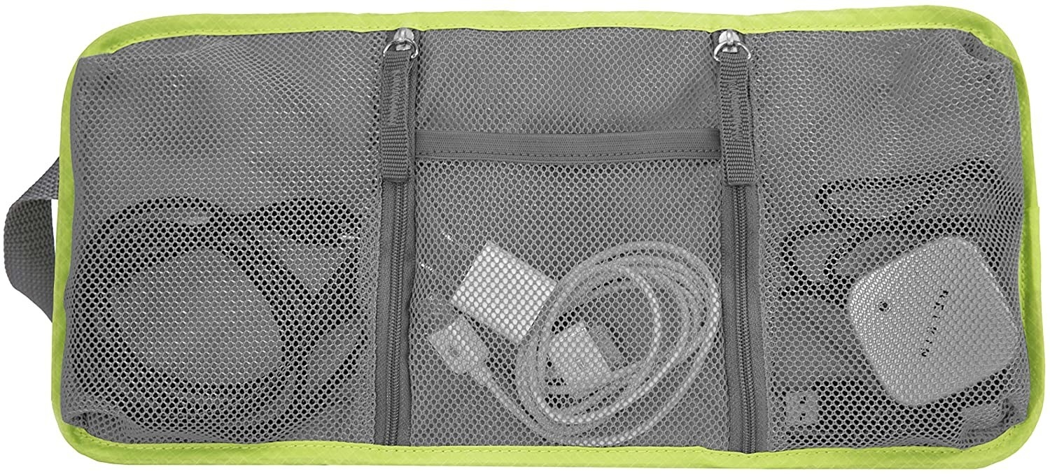 A small rectangular fabric case is open with three mesh pockets inside holding charging cords and plug adapters