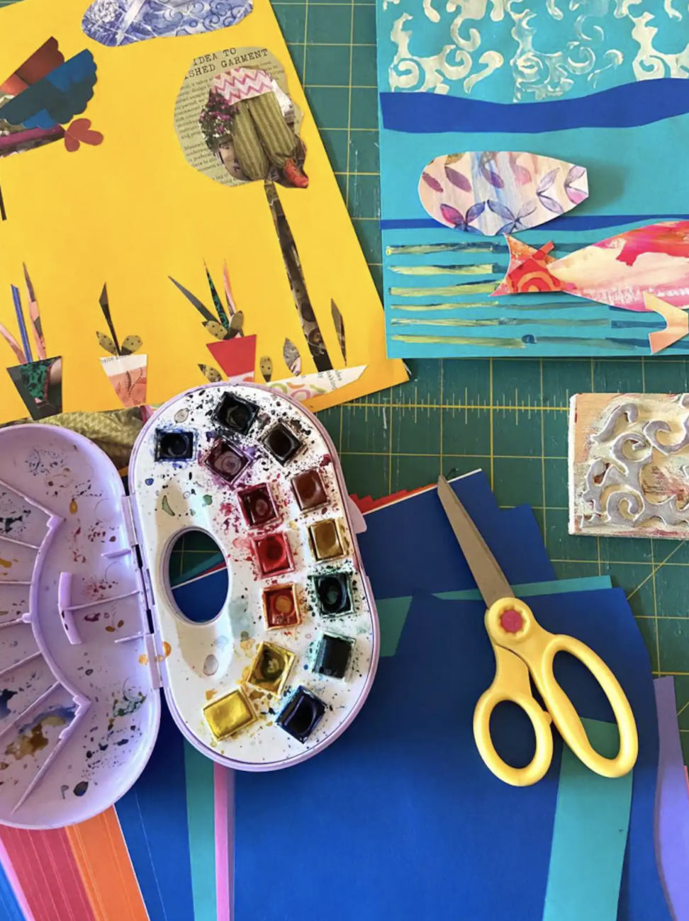 A top down shot of a table covered with colorful paper, scraps of paper material, scissors, and a used paint palette