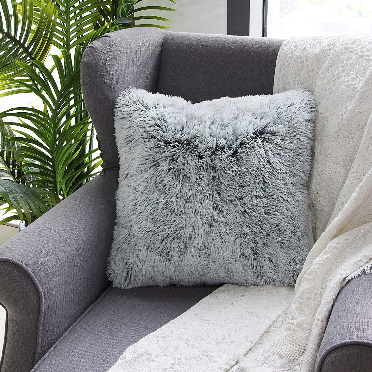 A grey faux fur square pillow on a chair