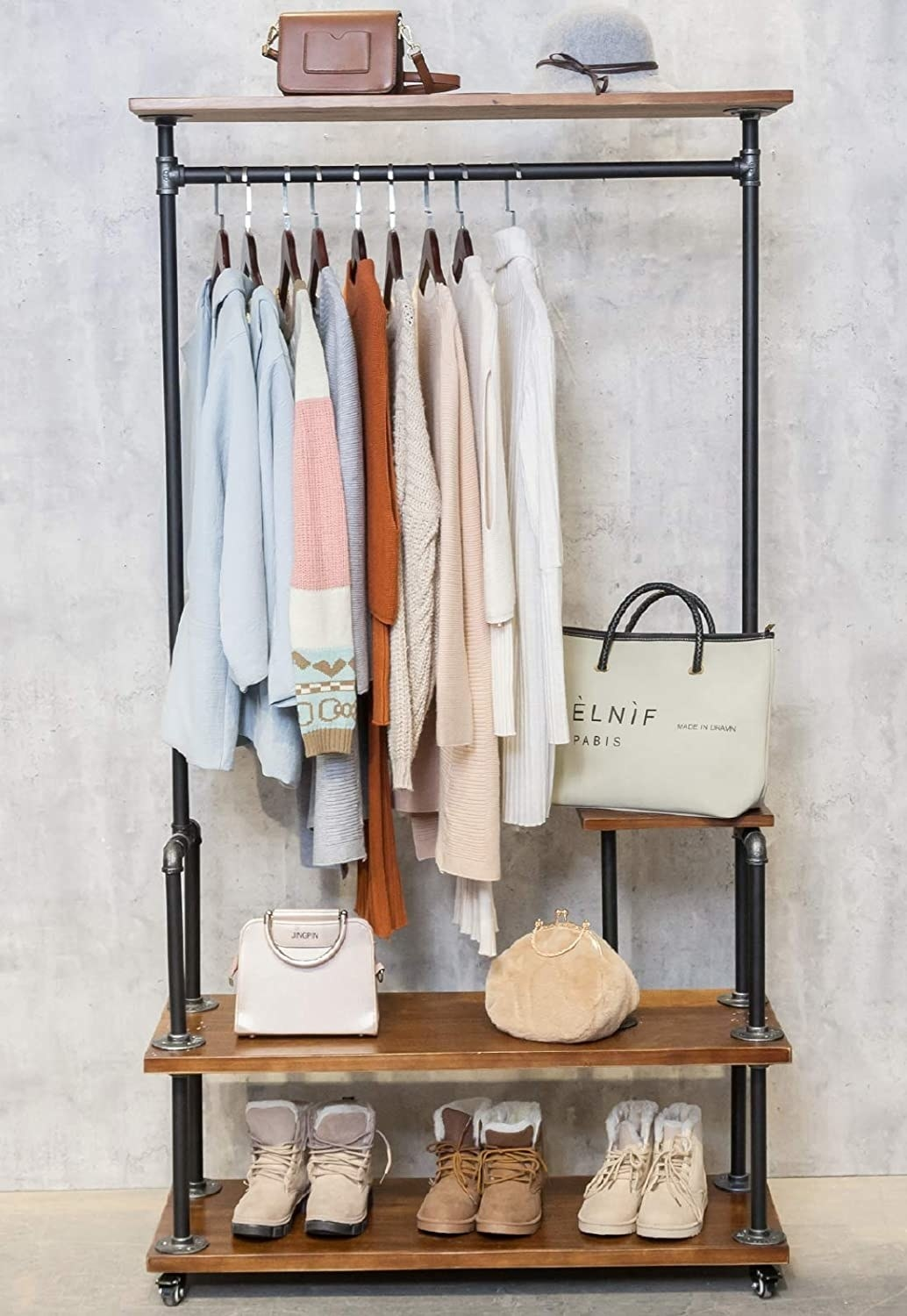 The garment rack with clothes on it and two wood shelves at the bottom with shoes and accessories and a shelf at the top with other accessories on it.