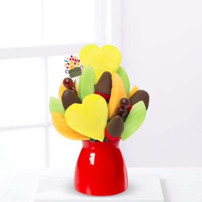 An Edible Arrangements mini bouquet with heart-shaped fruit and chocolate-dipped strawberries in a red vase