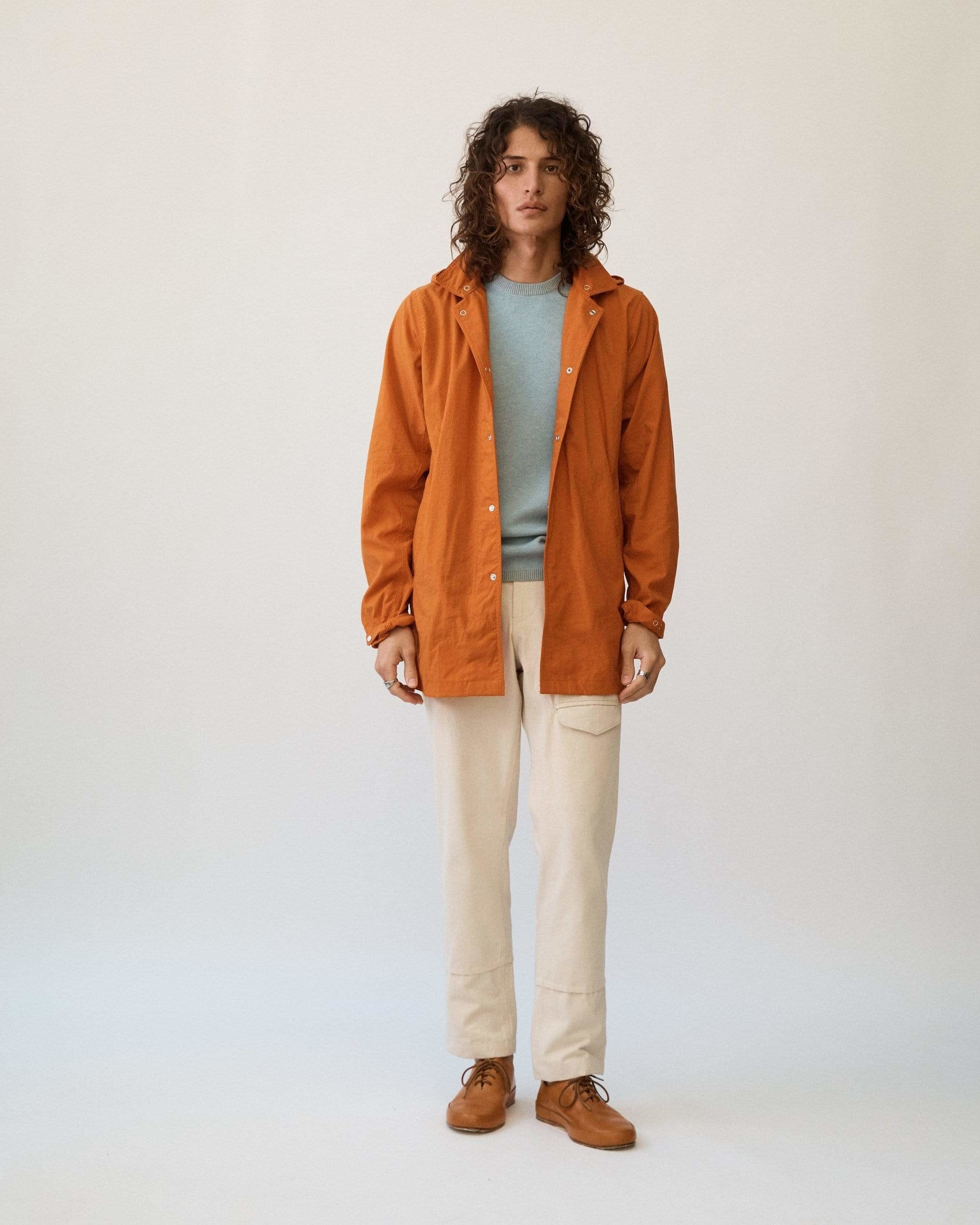Model wearing Corridor natural dye nylon rainjacket in orange