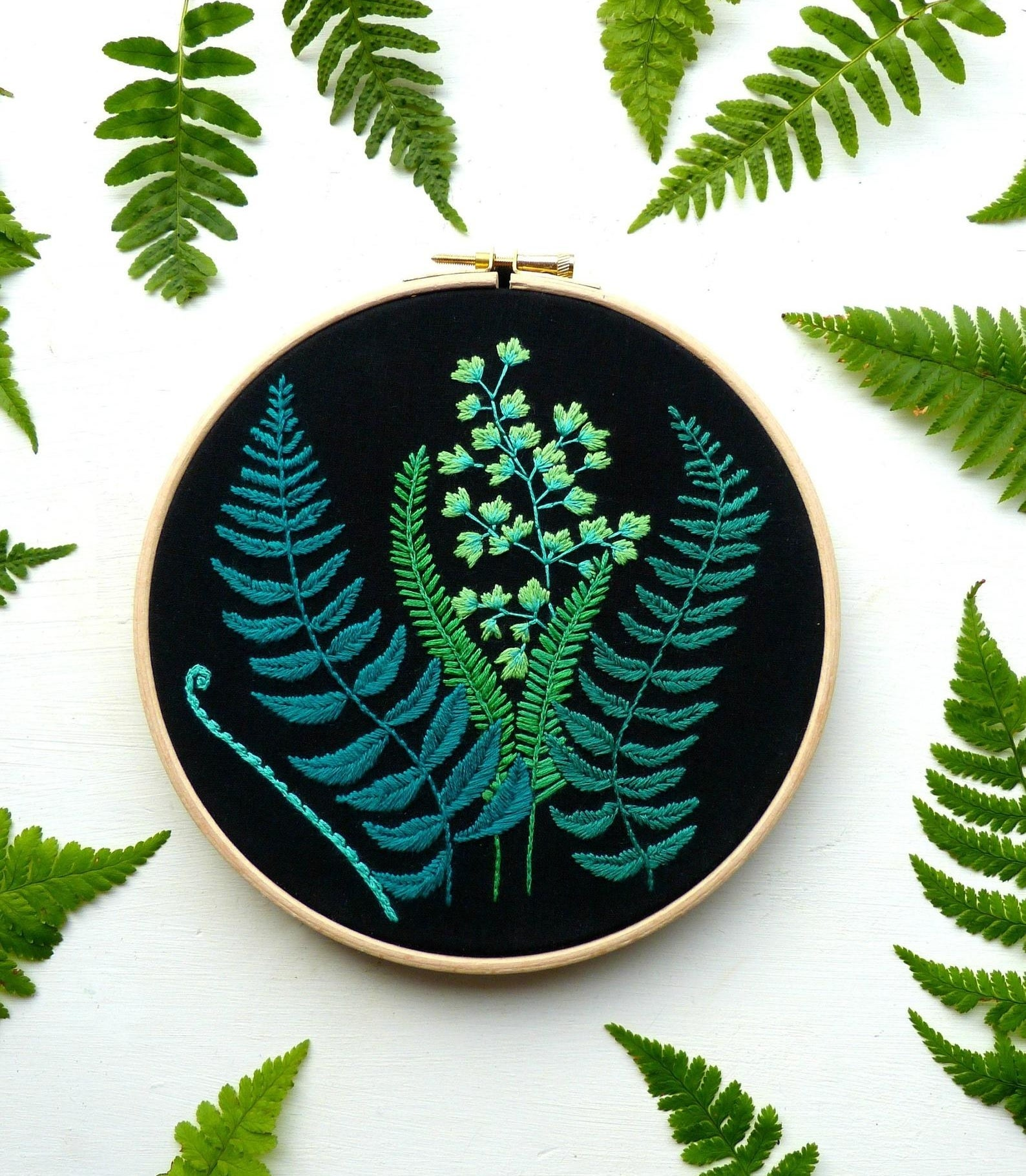 black fabric on a hoop with embroidered ferns and plants in various green shades