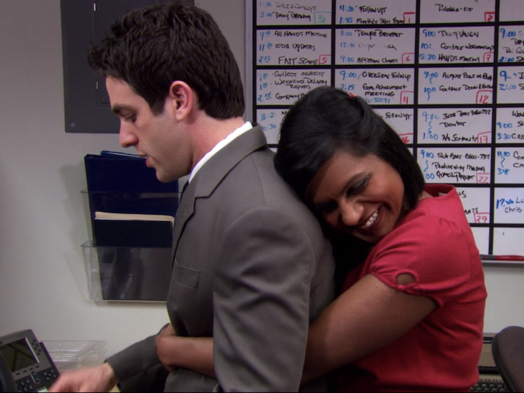 """""""The Office"""" character Kelly is seen hugging Ryan from behind, while smiling"""