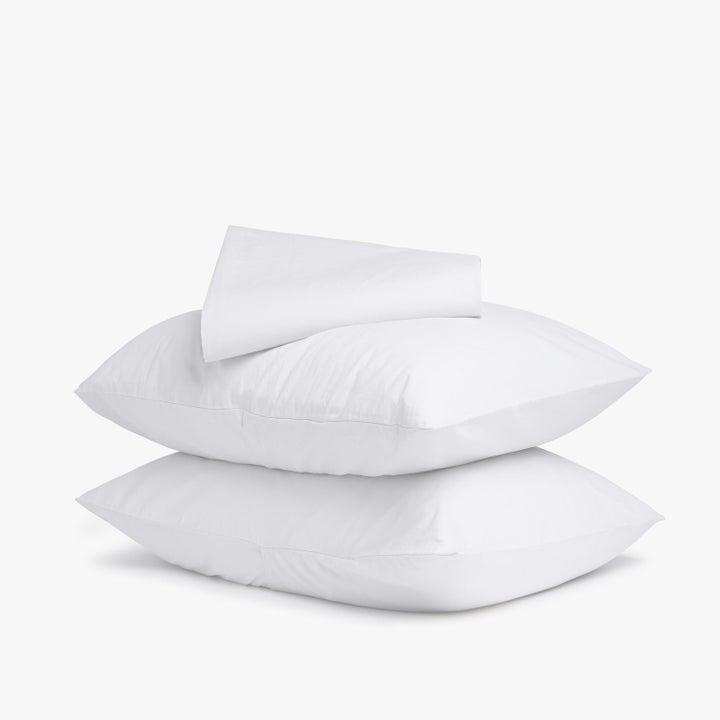 Two pillows with pillowcases plus a white sheet