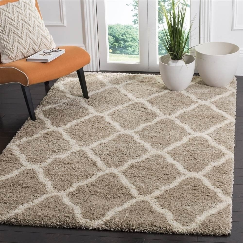 A taupe shaggy rug with diamond-shaped designs on it in white.