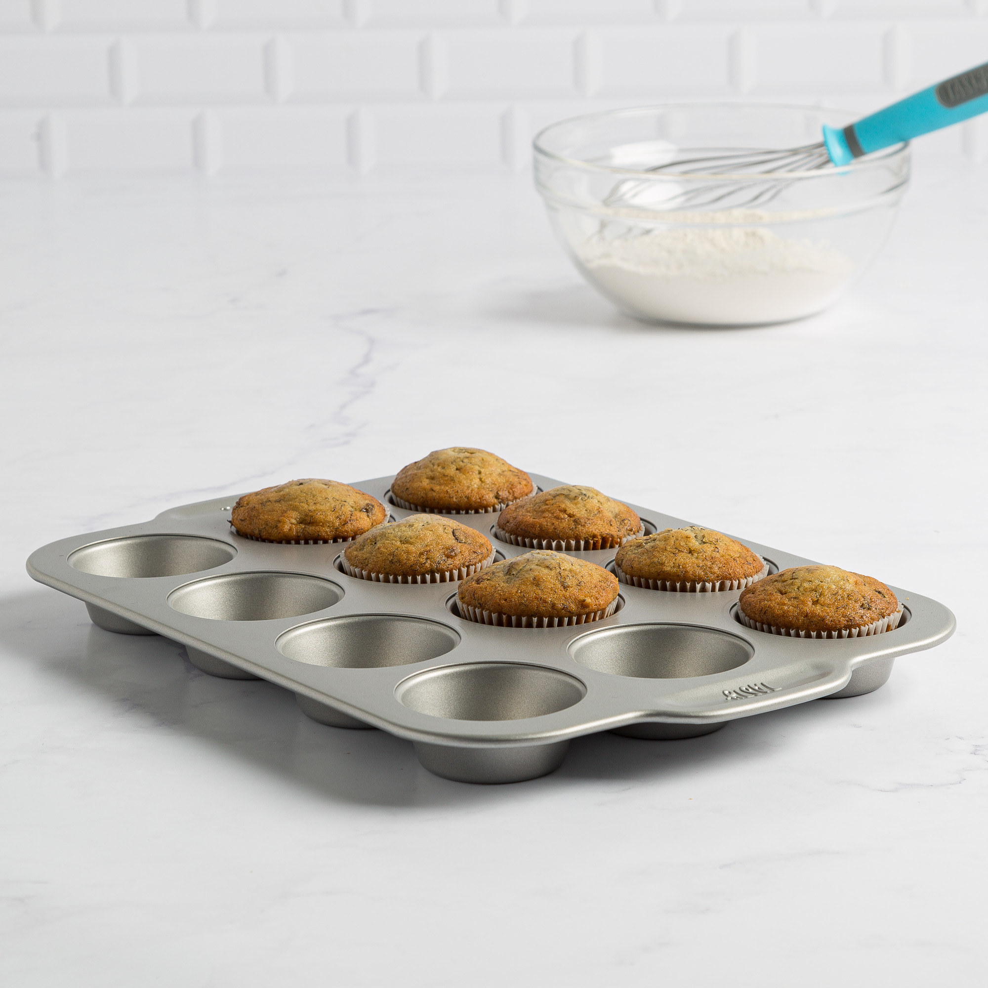 muffin tin on a white marble counter