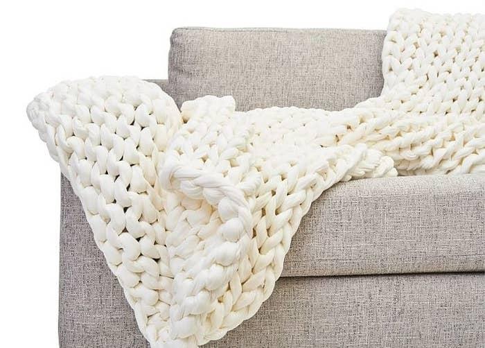 The white cotton knit blanket on a sofa