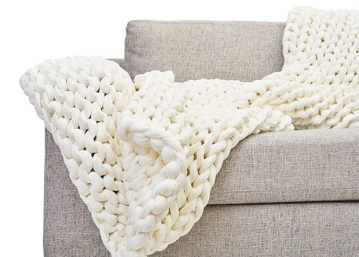 The white cotton knit blanket on a sofa