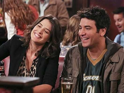 """""""How I Met Your Mother"""" characters Robin and Ted laughing, while sitting inside their local bar"""