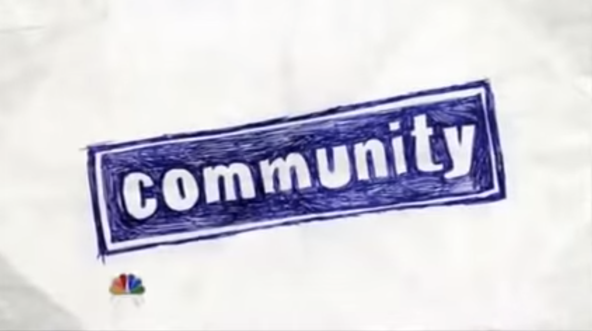 """Community"" title card — which is the title of the show in blue ink on a white sheet of paper."