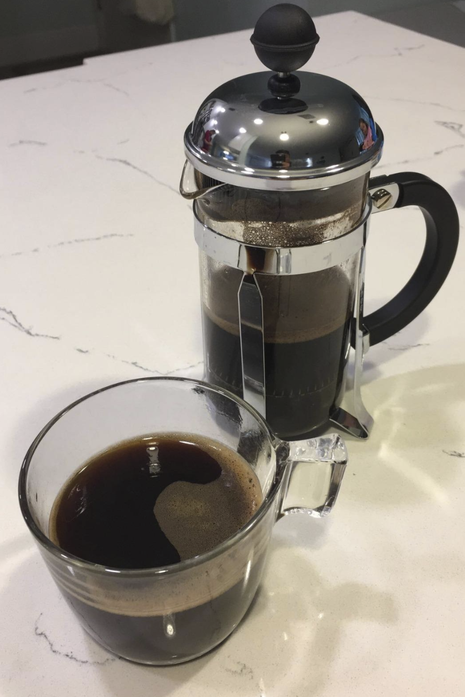 the press coffee maker which is shaped like a tall glass mug with a metal top sitting beside a glass mug of coffee