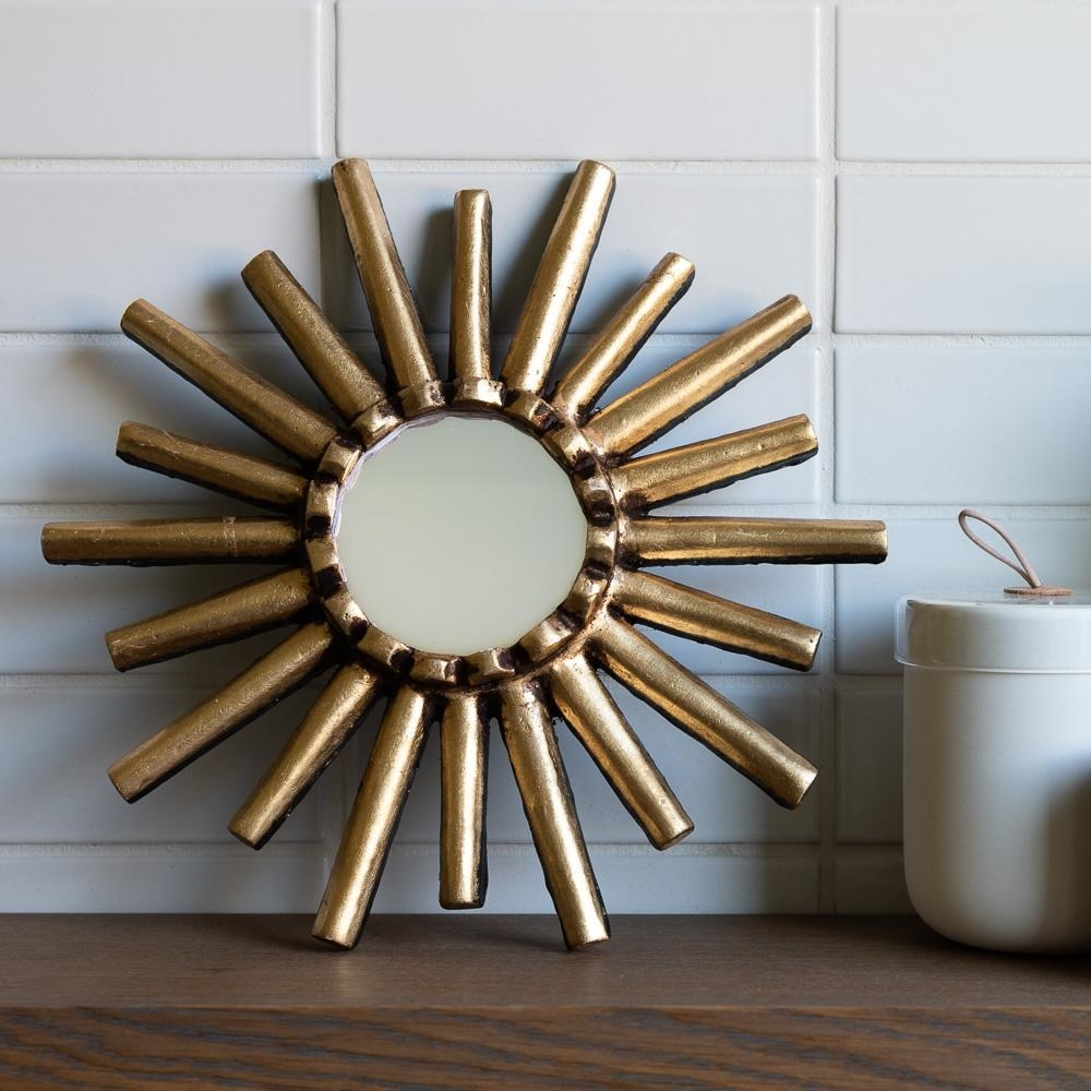 Small circular mirror with gold burst coming out all around it, making it look like the sun.