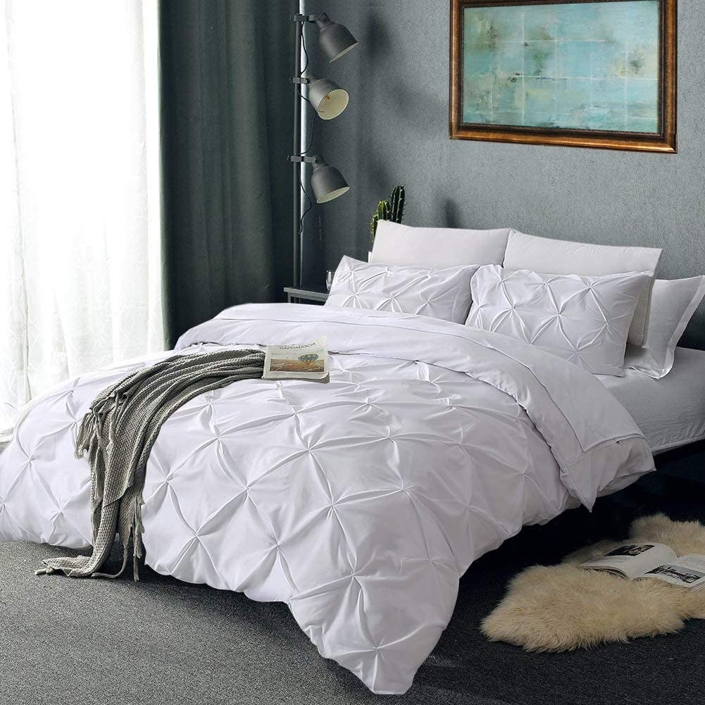 White duvet cover with pleats all over it and two pillow covers on a made bed.