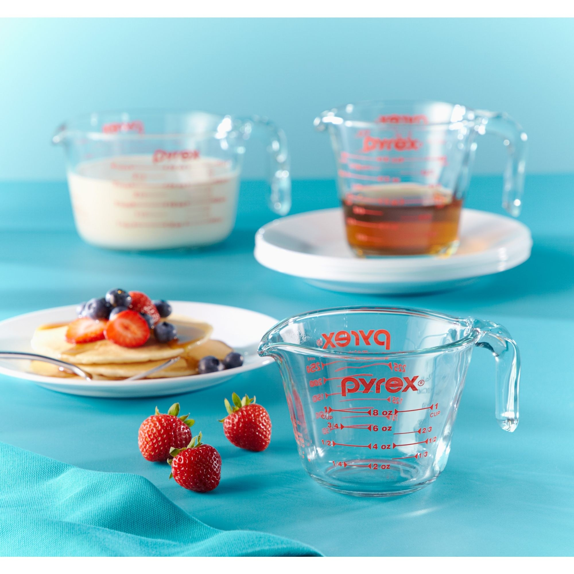 three pyrex measuring cups on a blue background