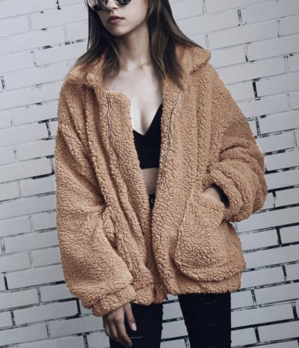Model in a zippered camel colored faux shearling jacket