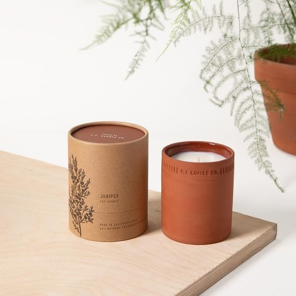 Soy wax candle in textured terra-cotta pot beside cylindrical packaging