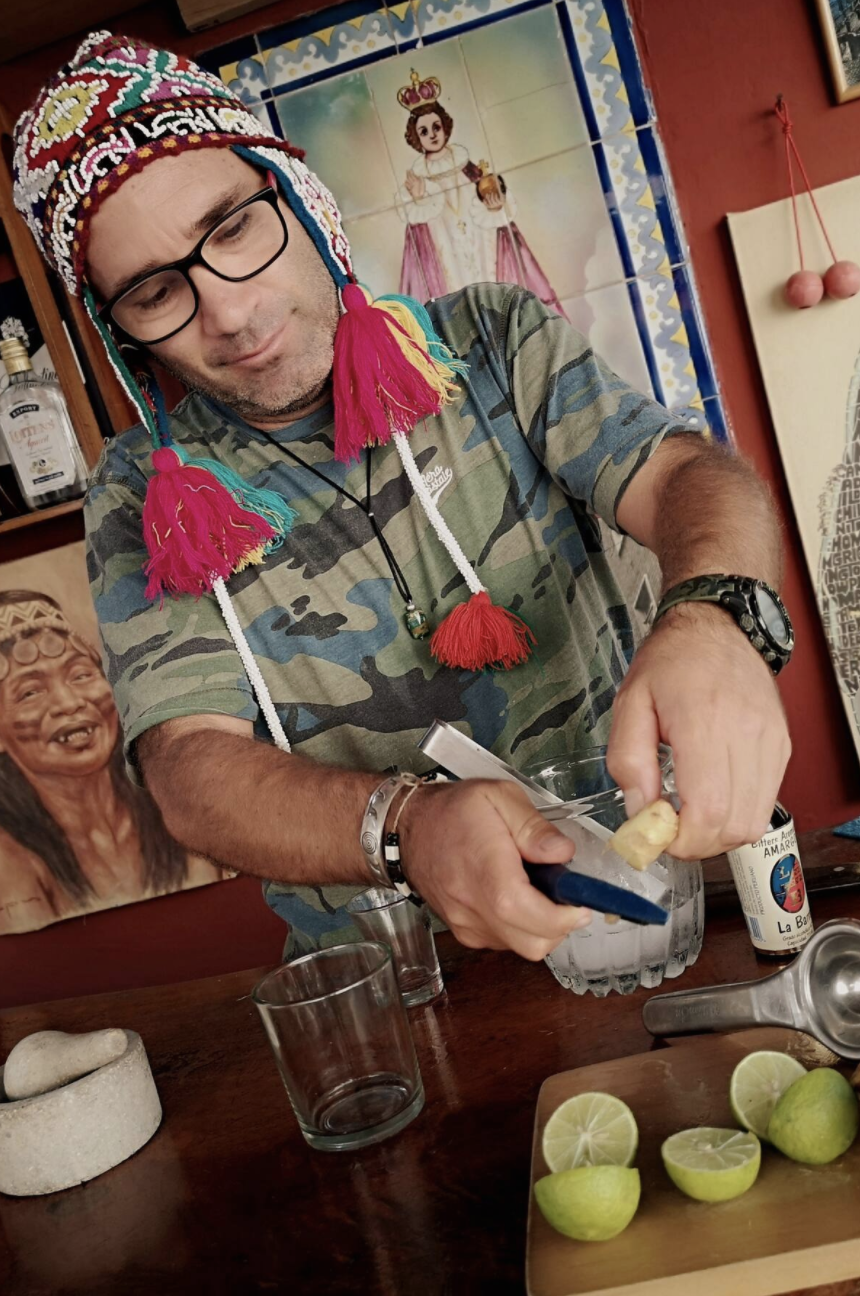 A man in a colorful patterned knit hat smiles down at the drink he is making