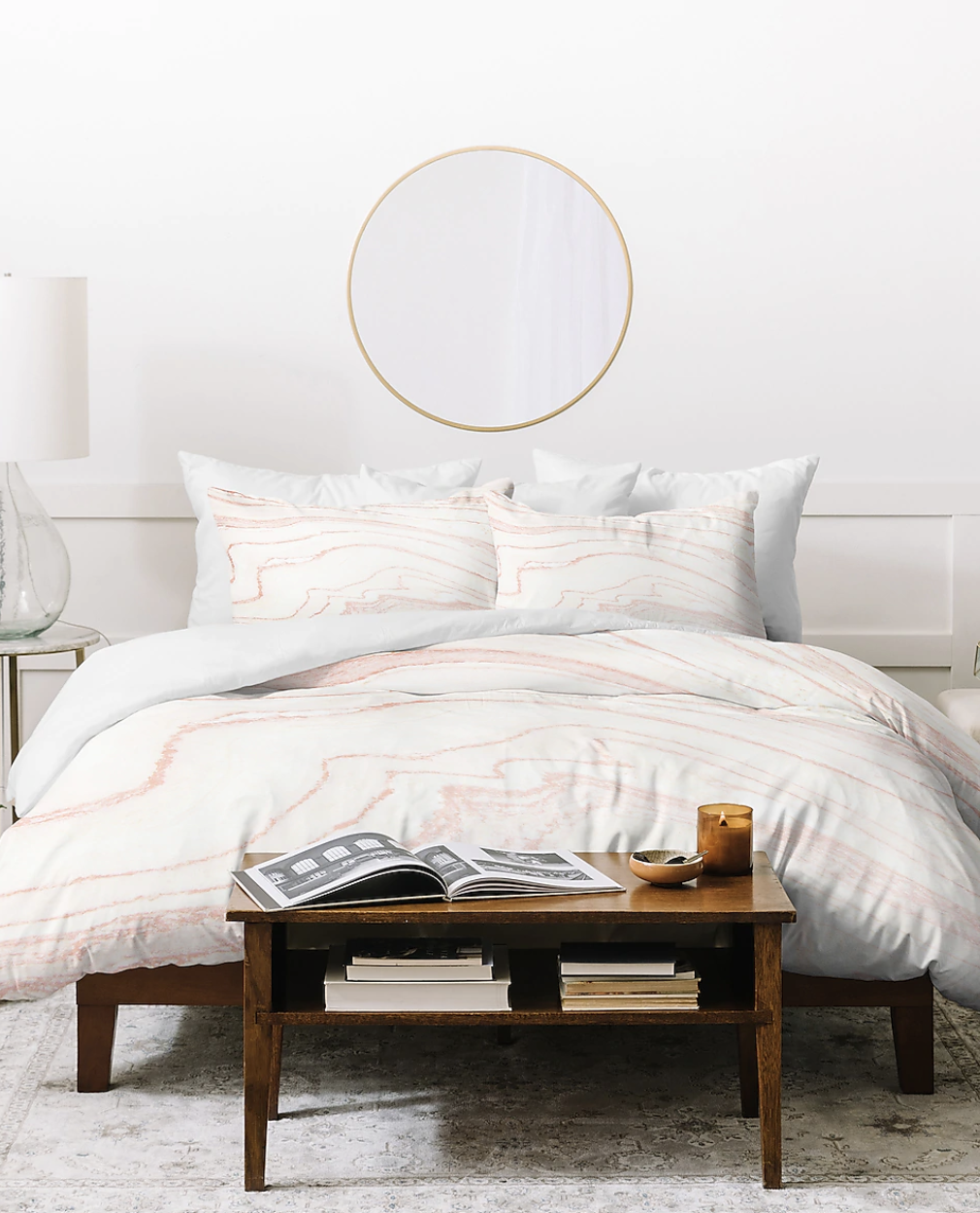 A pale pink and white marble patterned duvet set on a bed