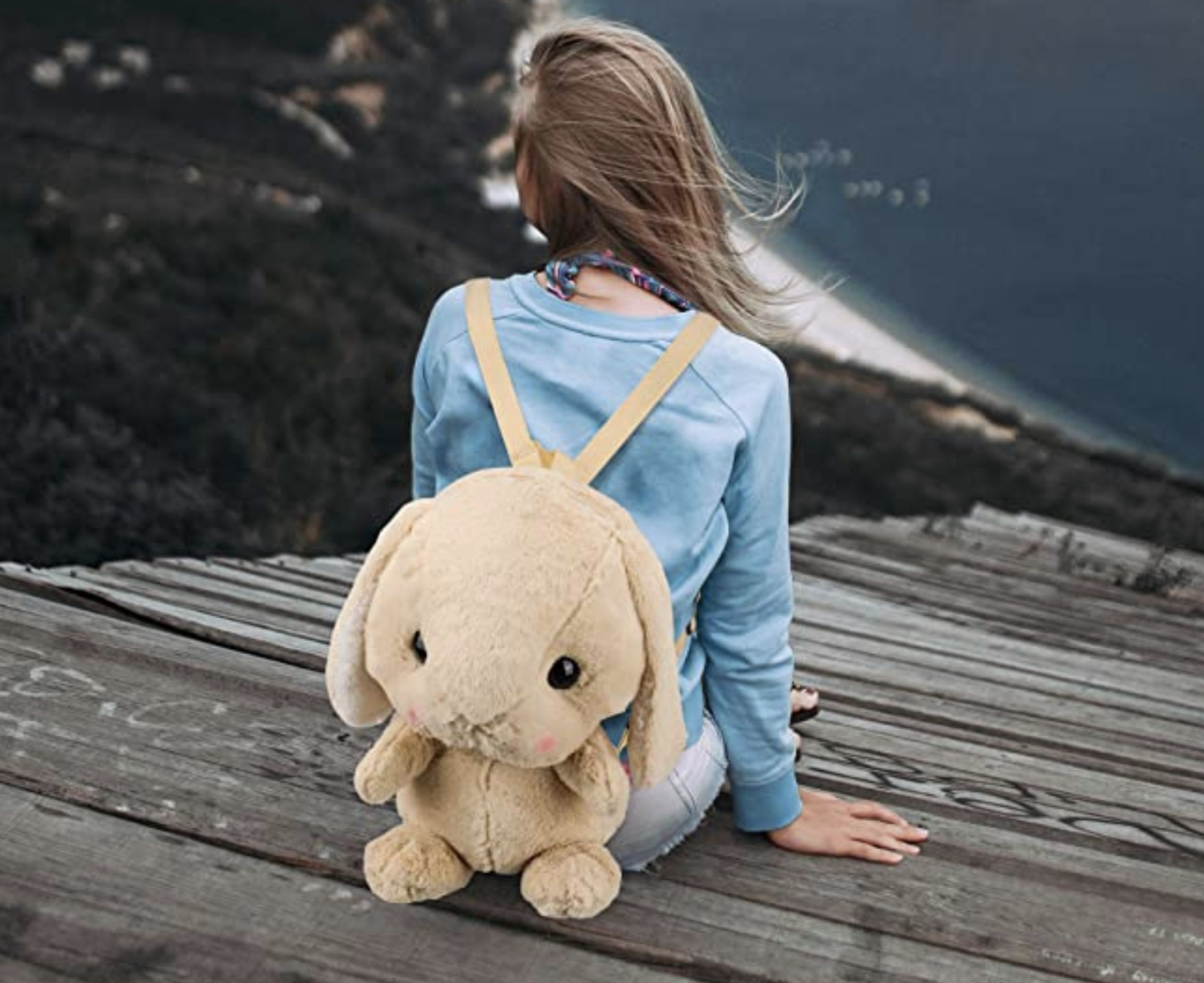 model wearing a beige plush bunny shaped backpack