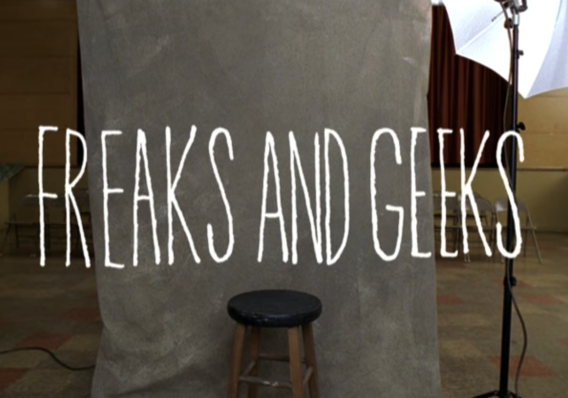 """Freaks and Geeks"" title card — which is the title over a school picture day backdrop."