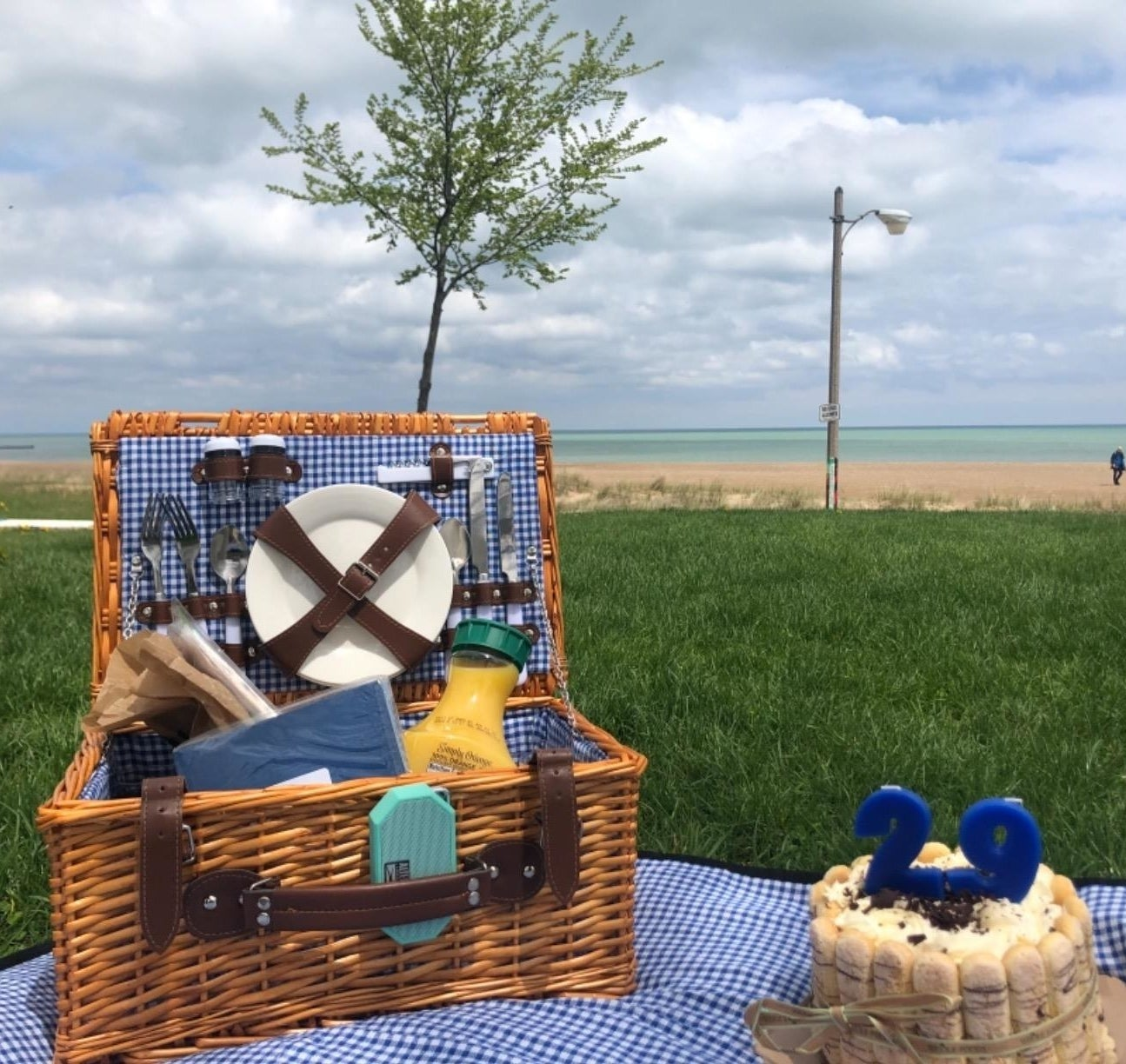 reviewer's open basket on a blanket at the beach with plates, etc strapped securely to the lid