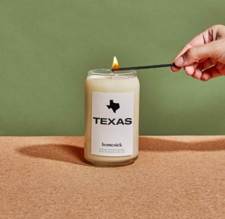 Hand holds match to light Texas Homesick candle on a table