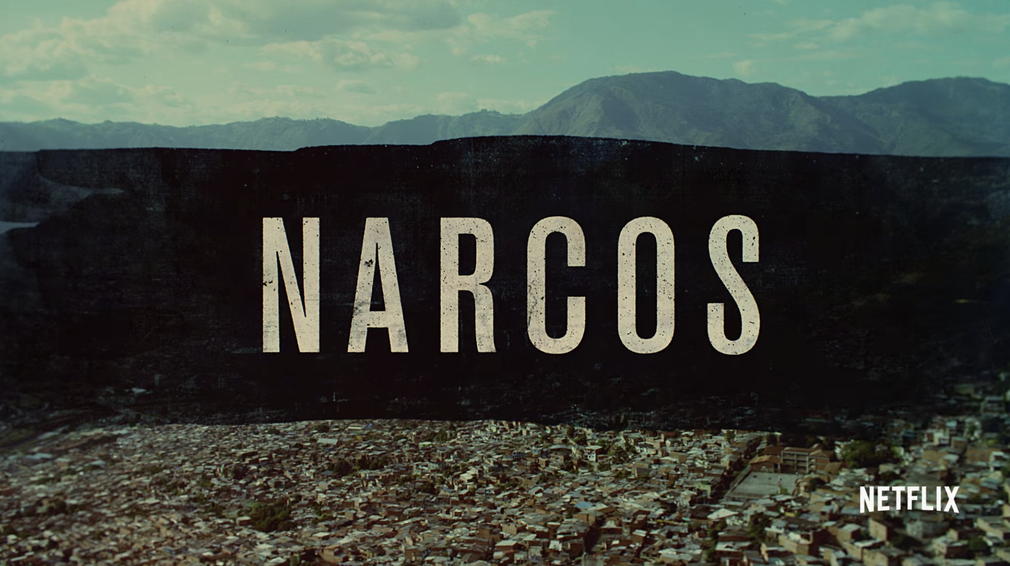 """Narcos"" title card — which is the title over a landscape of Colombia."