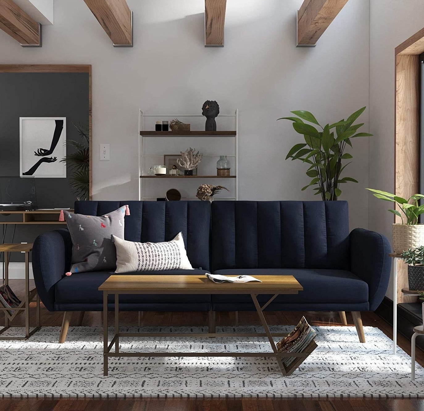 A navy blue futon with a tufted cushion back with slanted wooden legs in a living room.