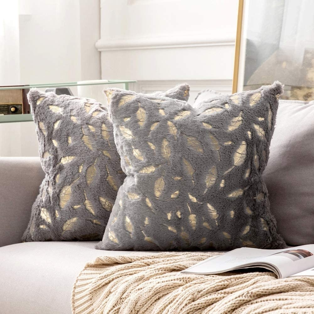 Two pillows on a couch with gild feathers