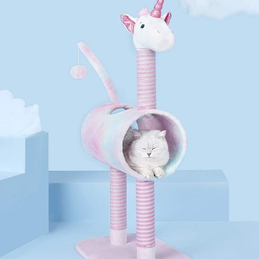 "The unicorn-shaped cat condo, with a pink base and two pink ""legs,"" a multi-colored fur tube, a ""tail"" with ball and string dangling from it, and a ""head"" with unicorn horn"