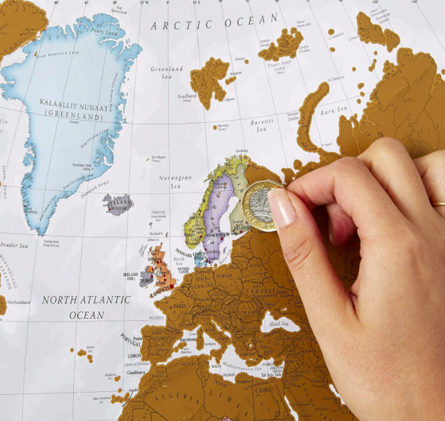 Hand uses coin to scratch off countries in Northern Europe on a scratch-off world map
