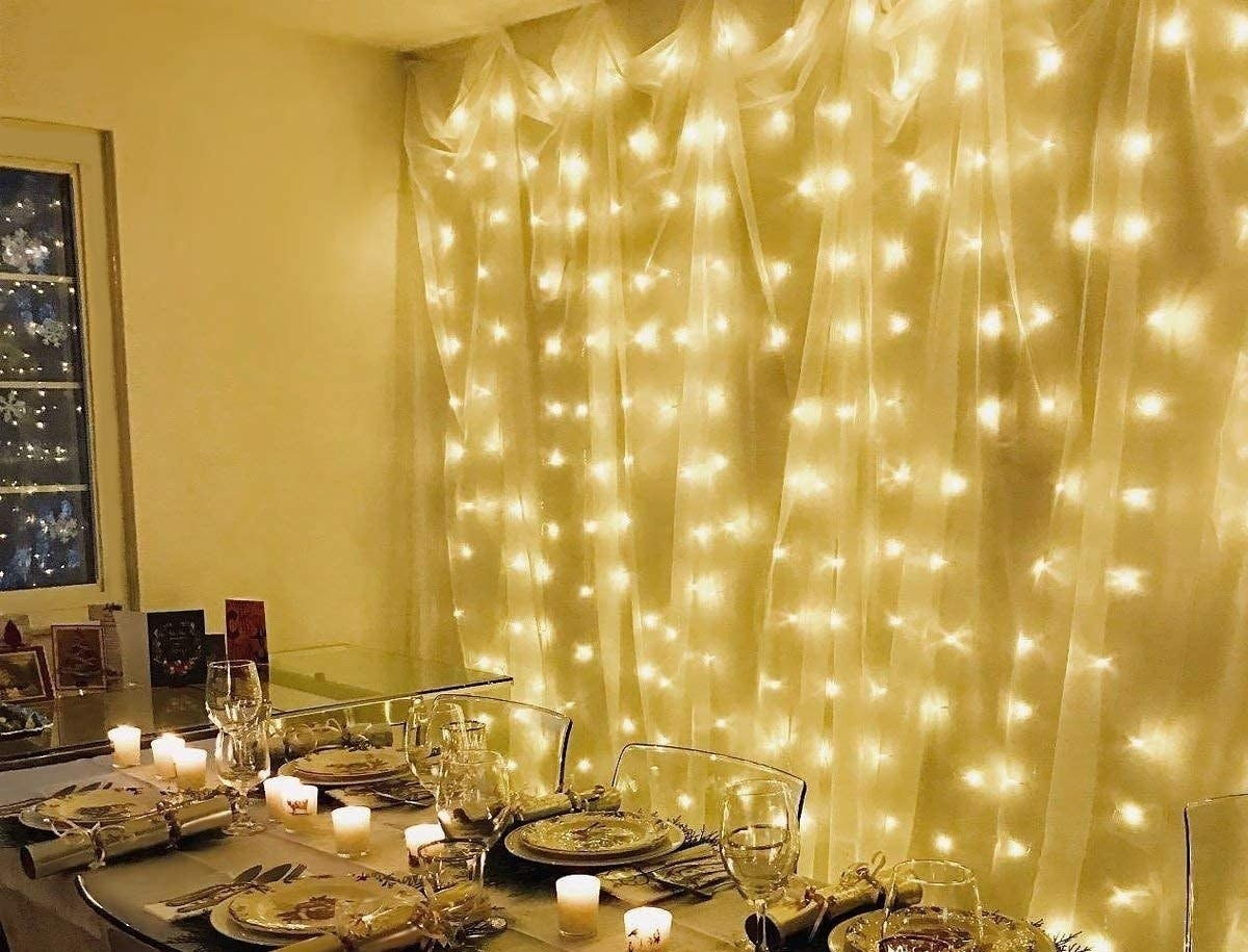 Fairy lights hung upon a wall beside a dinner table