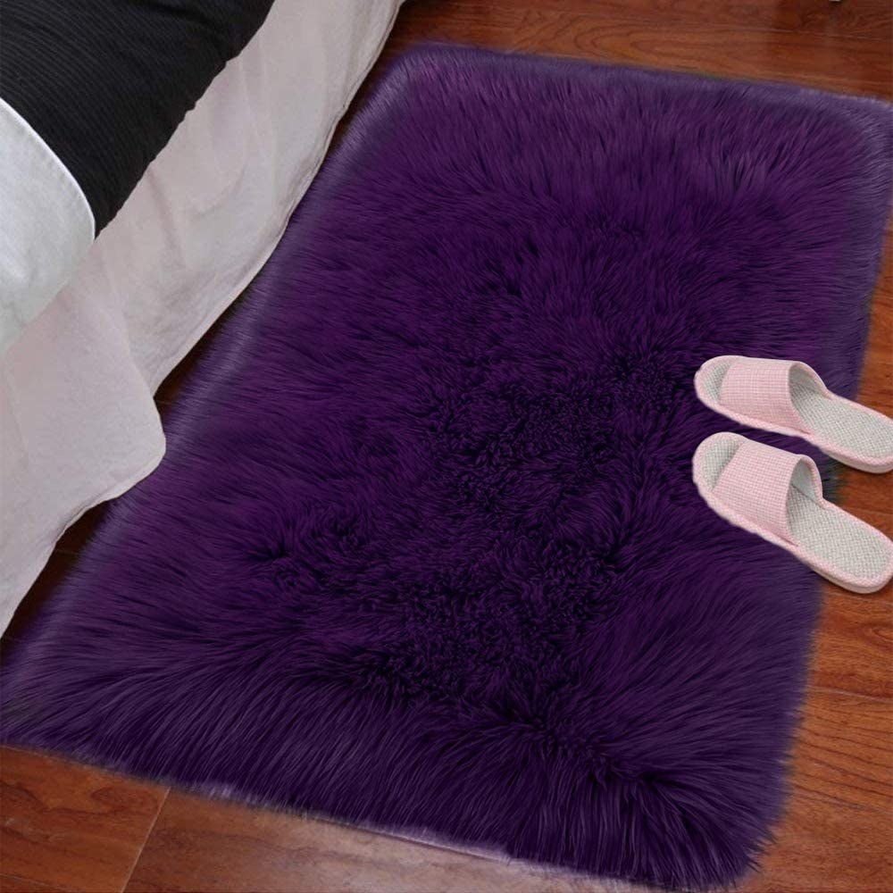 A fluffy rug beside a bed with slippers