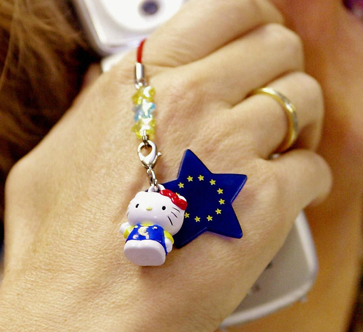 A photo of a handing holding a flip phone with Hello Kitty and E.U. charm on it