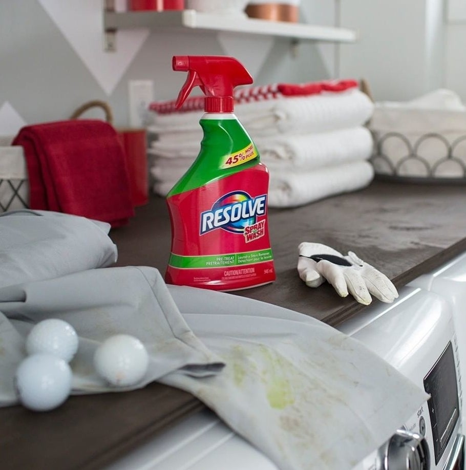 A bottle of the stain remover next to some grass-stained golf pants
