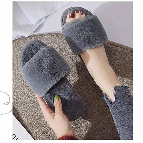 Person putting on grey fuzzy slippers.