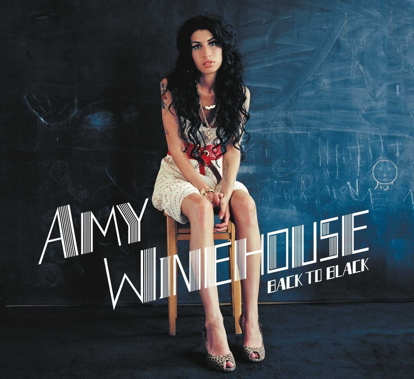 Amy Winehouse sitting on a stool in front of a chalkboard.