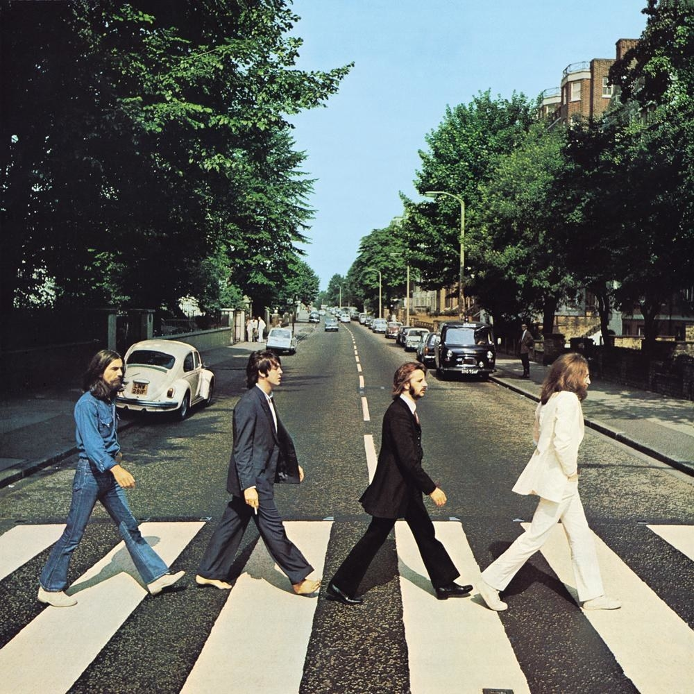 The Beatles walking across the crosswalk on Abbey Road in London.