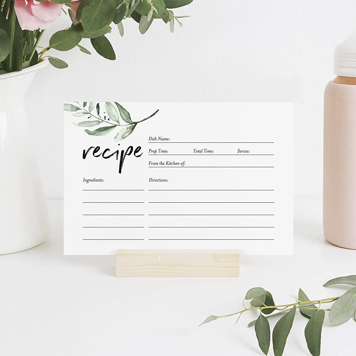A recipe card on a holder next to a plant and a water bottle