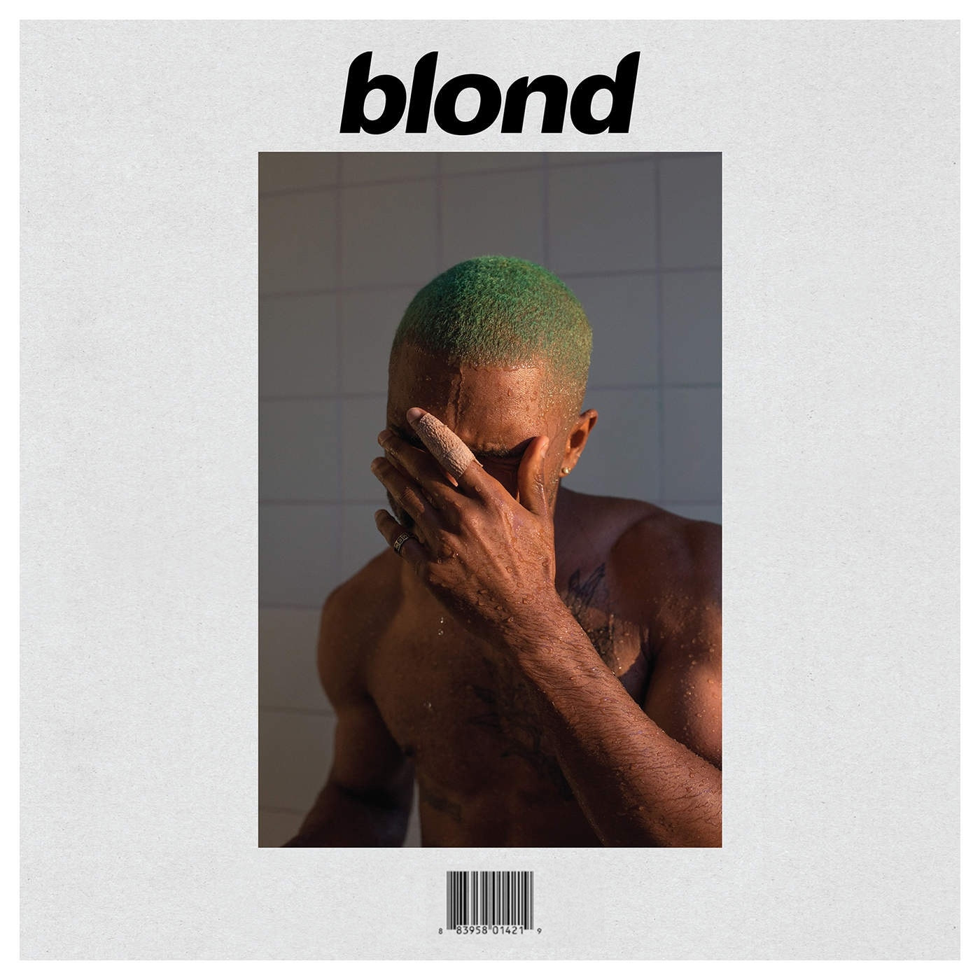 Frank Ocean, covering his face in the shower, with a green buzzcut.