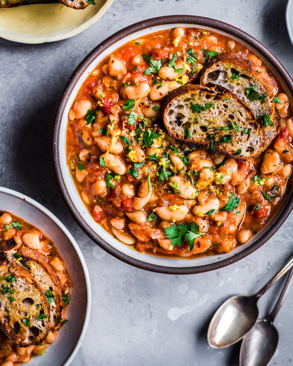 Two bowls of white beans in a tomato-based sauce topped with fresh herbs and sliced bread.