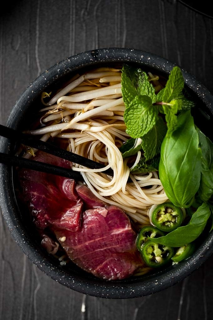 A bowl of pho with noodles, sliced rare beef, jalapeños, and basil.