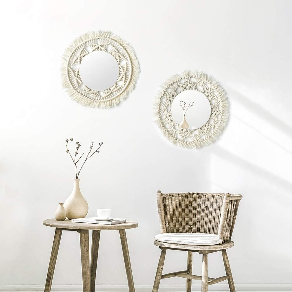 Two mirrors with macrame are hung on a wall