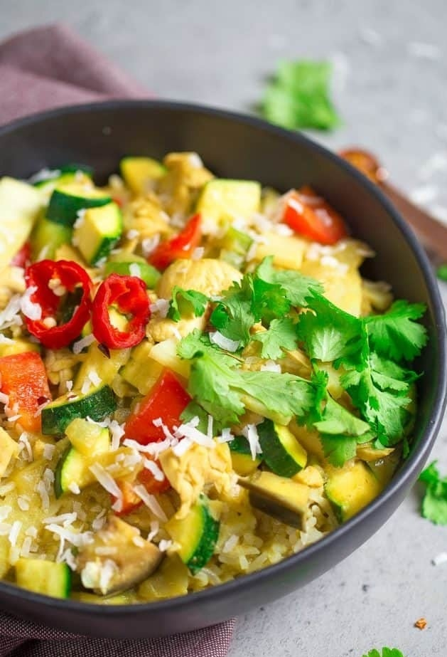 A bowl of Vegetable green curry with zucchini, peppers, and squash over rice with cilantro.
