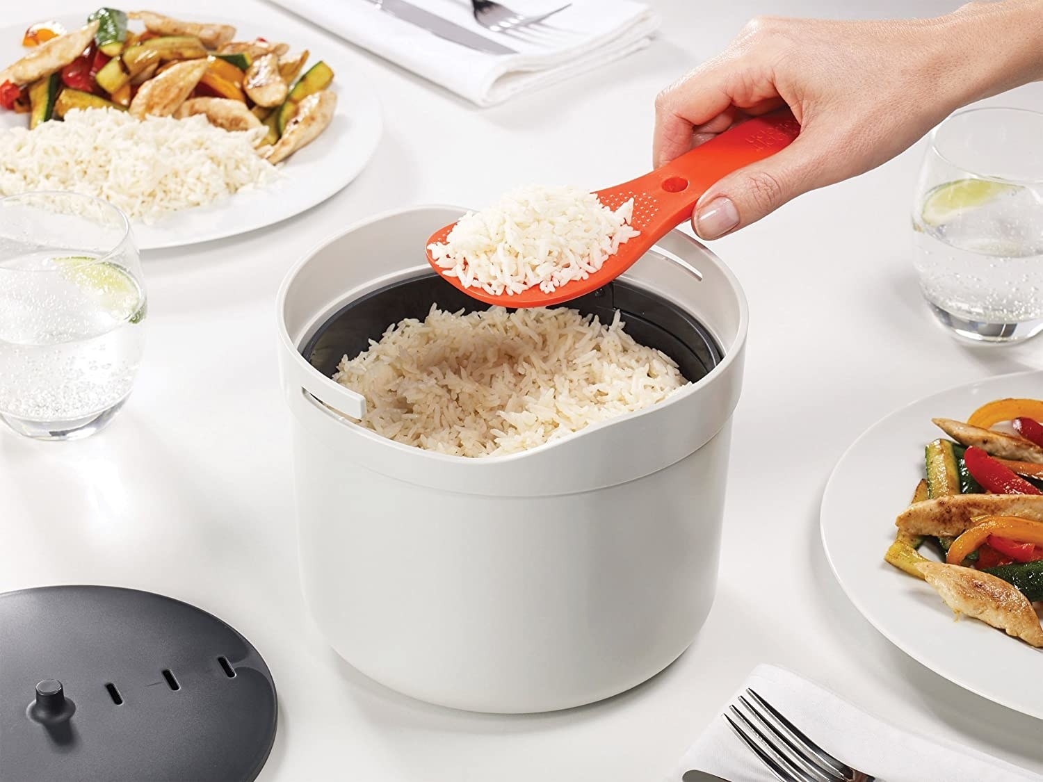 A person portioning out a spoonful of rice