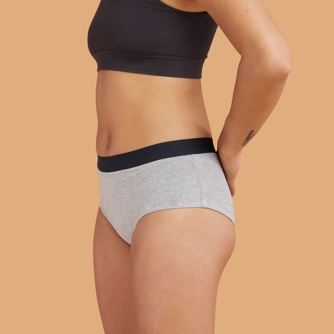 Model wearing the brief-style underwear in grey with a black band around the top.