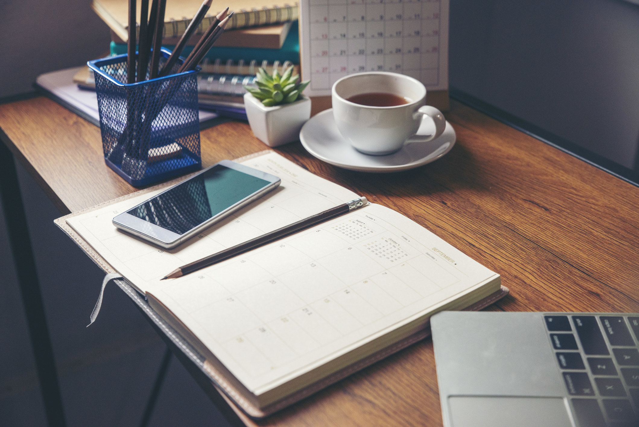 A desk with an open calendar and cell phone set on top of it.